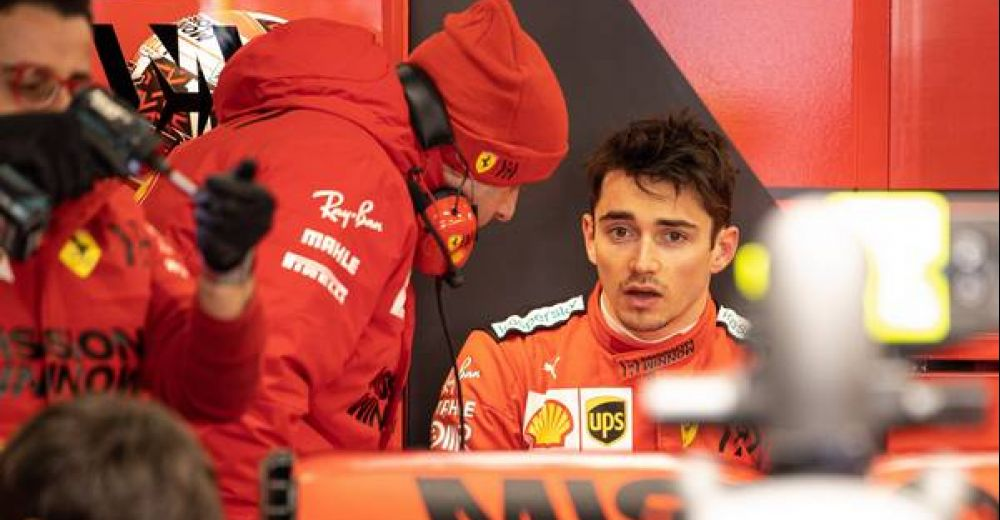 Charles Leclerc chats to an engineer in his Ferrari garage - maybe about how to beat Mercedes?